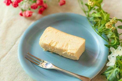 Light blue plate, baked cheesecake and flowers on a linen tablecloth