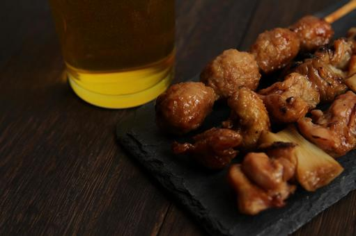 Beer and yakitori set placed on a wooden table