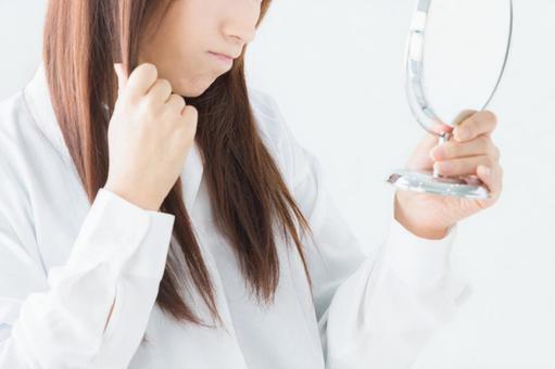 거울로 머리를 검사하는 여성