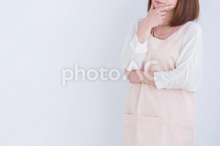 考えるエプロン姿の女性の写真