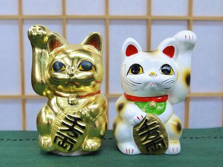 Two side-by-side beckoning cat piggy banks