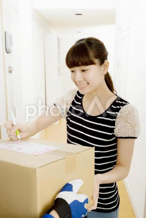 荷物の受取のサインをする女性2の写真
