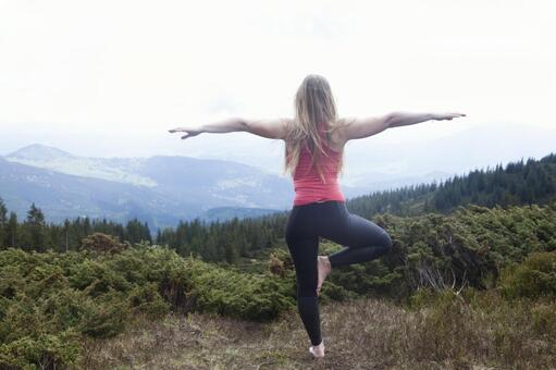 A woman who plays yoga at the top of a mountain 4