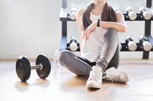 Asian woman taking a break in the training gym