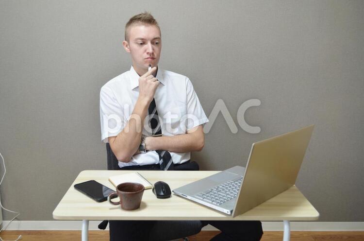 パソコン仕事で悩んでいる男性の写真