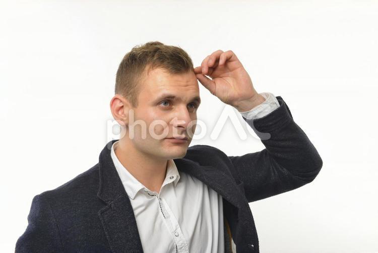 髪の毛が気になる外国人男性の写真