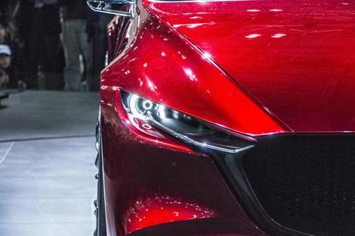 A car headlight photo (MAZDA KAI · Saki concept). An image impressive with a deep red color that drifts a sense of quality.