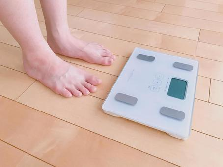 A person trying to get on a scale