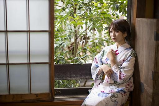 Yukata woman sitting by the window and staring