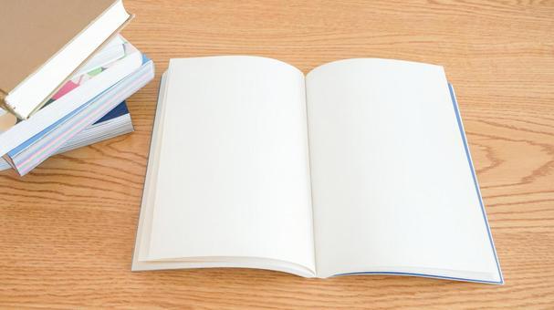 木紋桌上有一本打開的筆記本(書),供閱讀和學習的圖片素材(疊書)
