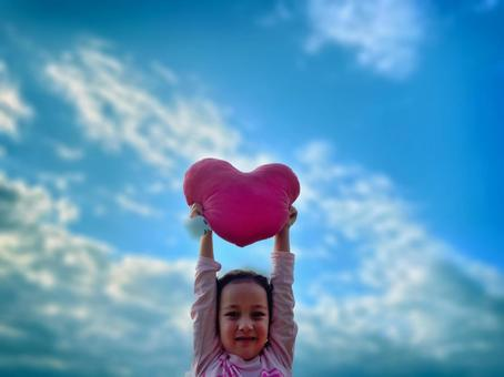 Girl lifting a heart cushion in the blue sky