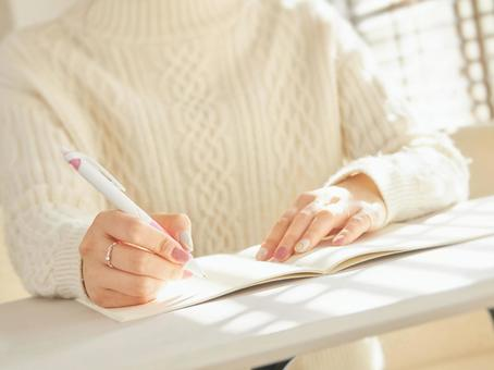 Image of a woman taking notes in a notebook