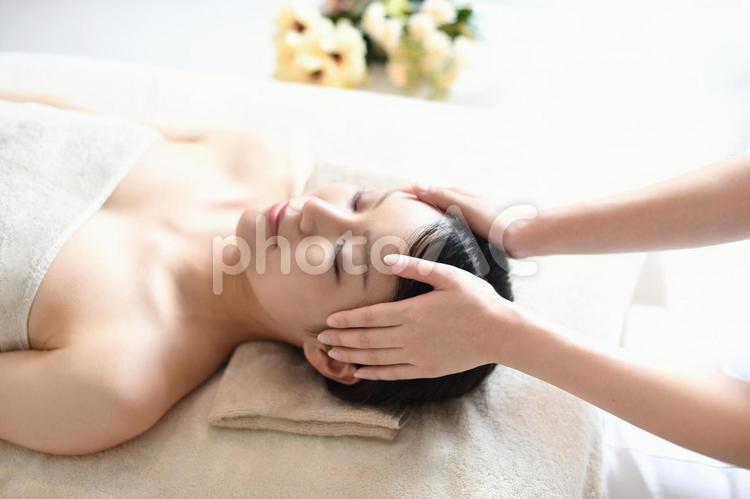 エステサロンでヘッドマッサージの施術を受ける若い女性の写真