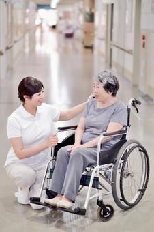 屋内で車椅子に乗っているおばあちゃんと介護士3