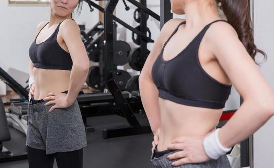 Woman checking body line in gym