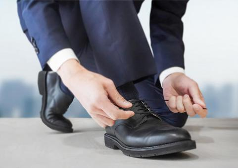 A businessman tying shoelaces