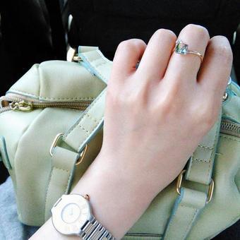 指輪と時計をした女性がカバンを持つ手