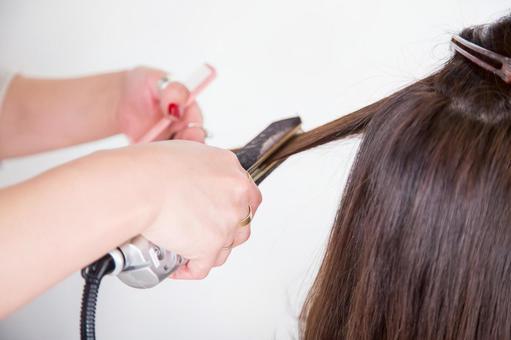 使用頭髮鐵的美髮師