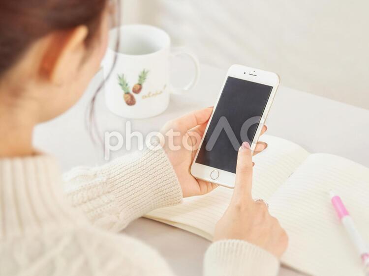 スマホをさわる女性のイメージの写真