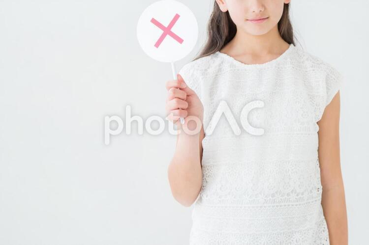 バツを持つ女の子の写真