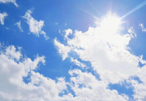 The shining sun between the clouds in the blue sky