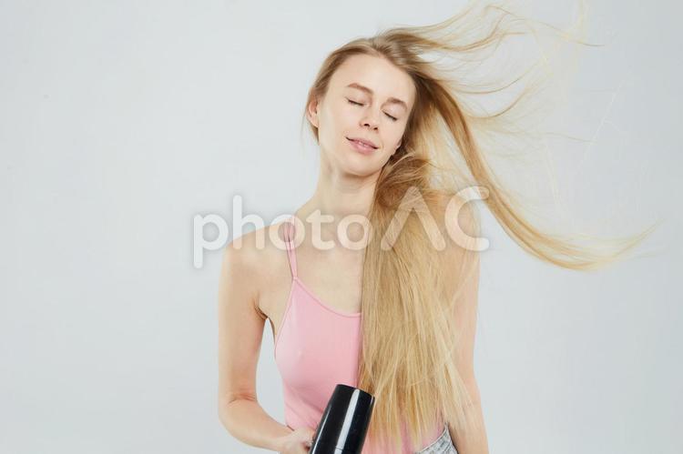 ドライヤーで髪を乾かす女性2の写真