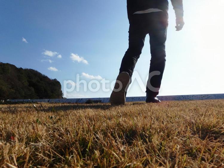 光へ向かって歩き出す人 男性 旅立ち イメージの写真