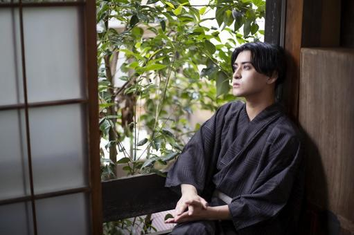 Yukata man sitting by the window and looking up at the sky