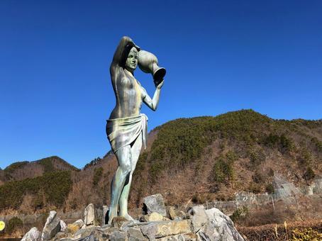 물동이를 가진 여성의 동상과 푸른 하늘