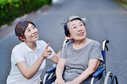 Grandmother and caregiver walking in a wheelchair 1