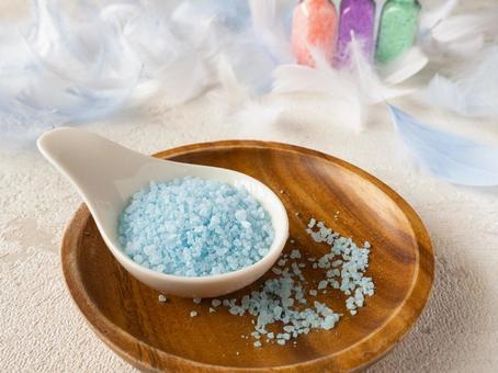 Light blue bath salts placed on a wooden plate