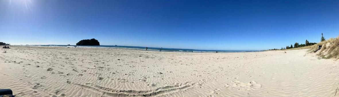 Beach panorama with white sand and deep blue sky (New Zealand)