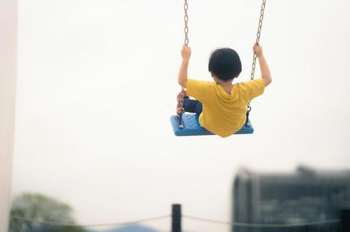 Back view of a child playing on a swing