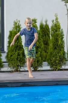 Boy 5 jumping into the pool