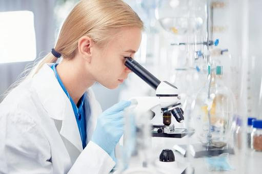 Researcher looking through a microscope 3