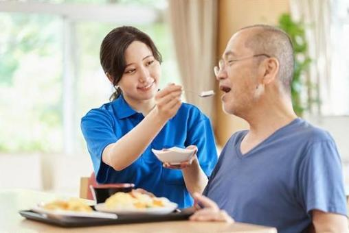 A caregiver who assists the elderly with meals