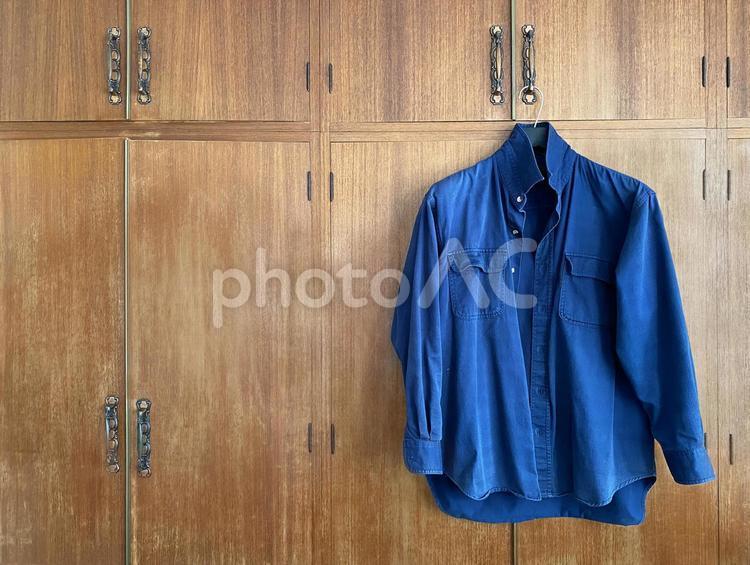 クローゼットの扉にかけられたデニムシャツの写真
