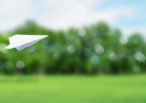 종이 비행기와 녹색 반짝이 배경