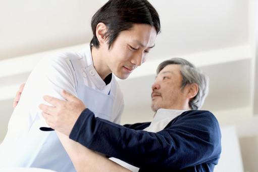 Caregiver teacher waking up an elderly man in bed
