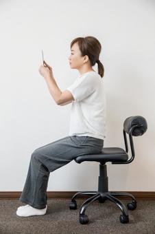 一個看著智能手機姿勢很好的女人