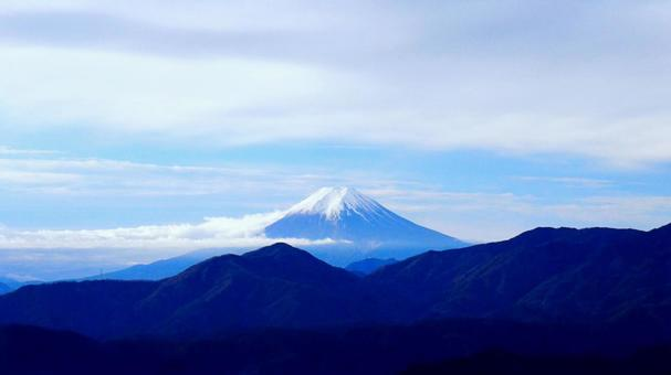 Fantastic Mt. Fuji covered with mountains and clouds
