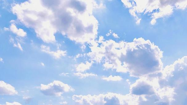 A sky background with lots of clouds that reflect the sun's rays and shine