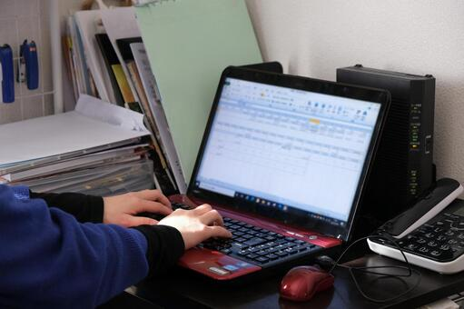 Female hand operating a laptop ② A pile of documents