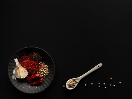 Red pepper and garlic black background on a small black plate
