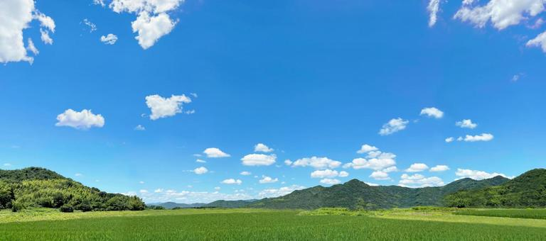 Clear blue sky, meadows and mountains panorama