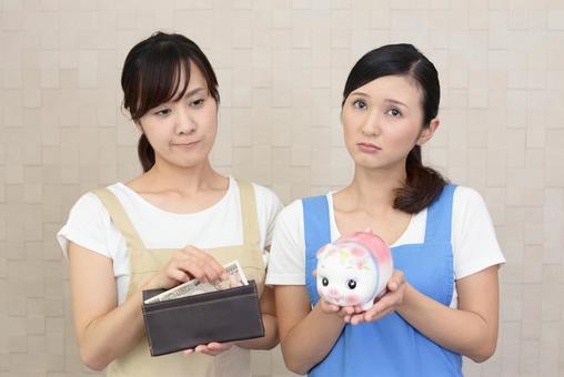 お金を持つ不安そうな表情の二人の女性
