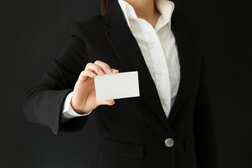 A woman holding a business card (card) with one hand