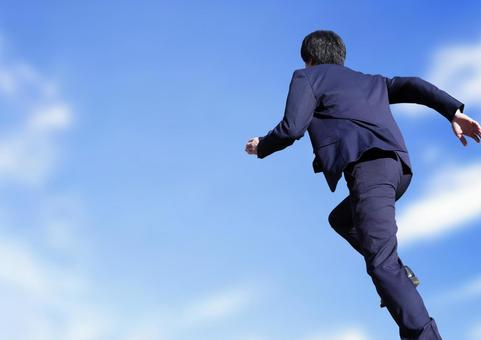 Running businessman sky background
