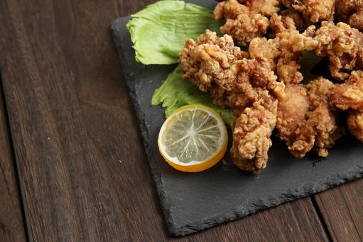 Lettuce, fried chicken and lemon placed on a wooden table