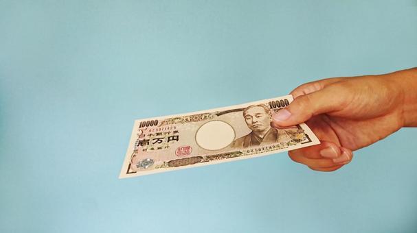 Hand giving a 10,000 yen bill _ Blue background
